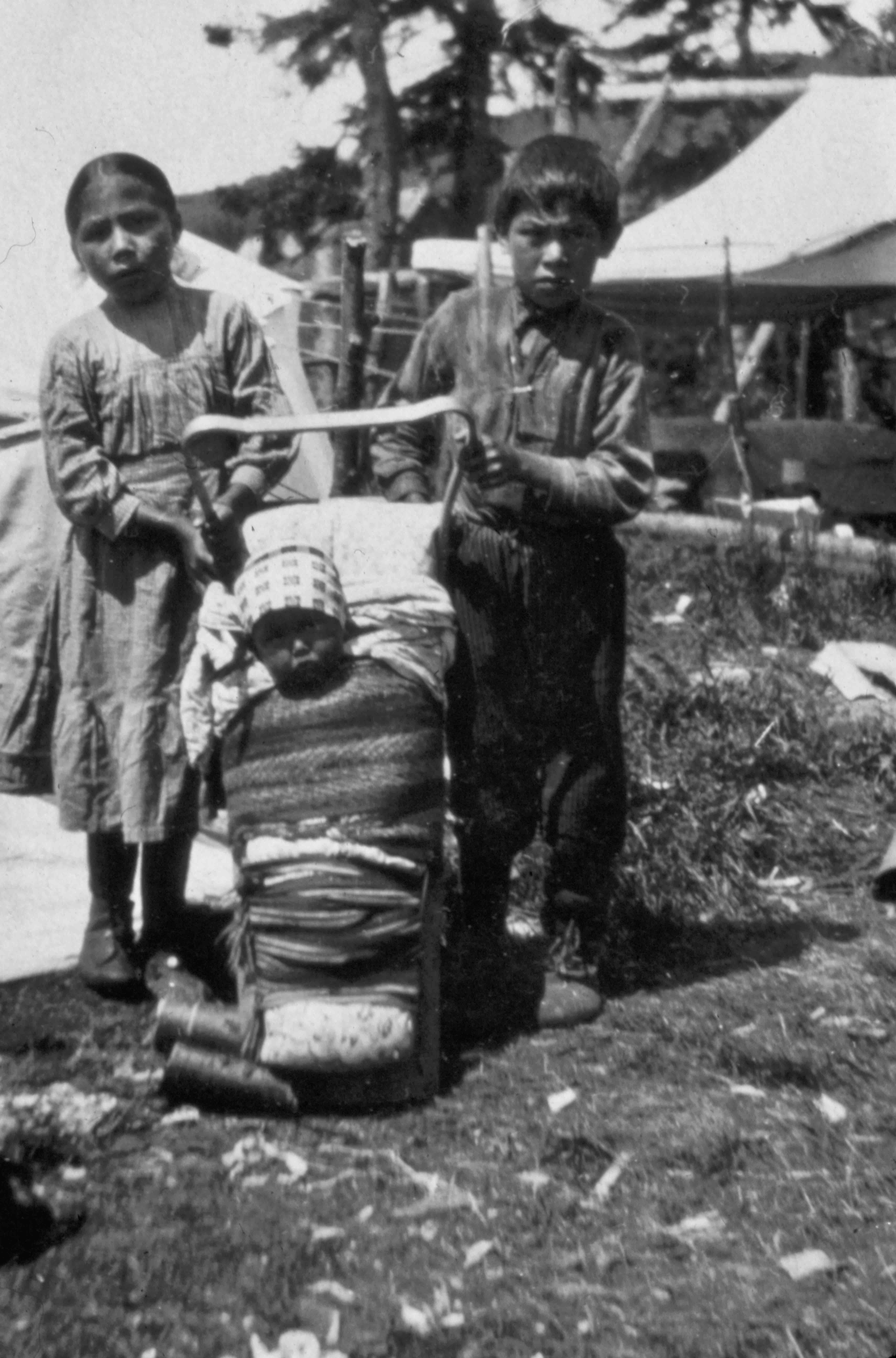 Enfants avec bébé dans tikinagan