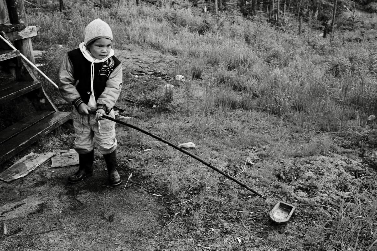 Enfant Atikamekw jouant avec un canot miniature