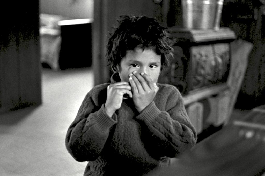 Jeune garçon Atikamekw à l'harmonica